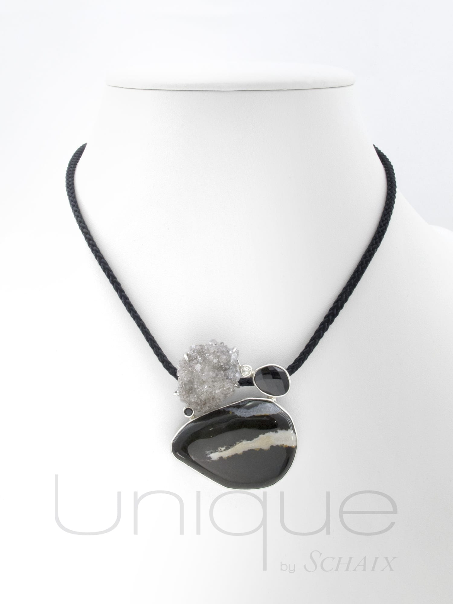 Silk thread with silver pendant enhanced by a crystallized quartz,a black and white baroque chalcedony cabochon, a faceted onyx and a cut crystal. Silver clasp.