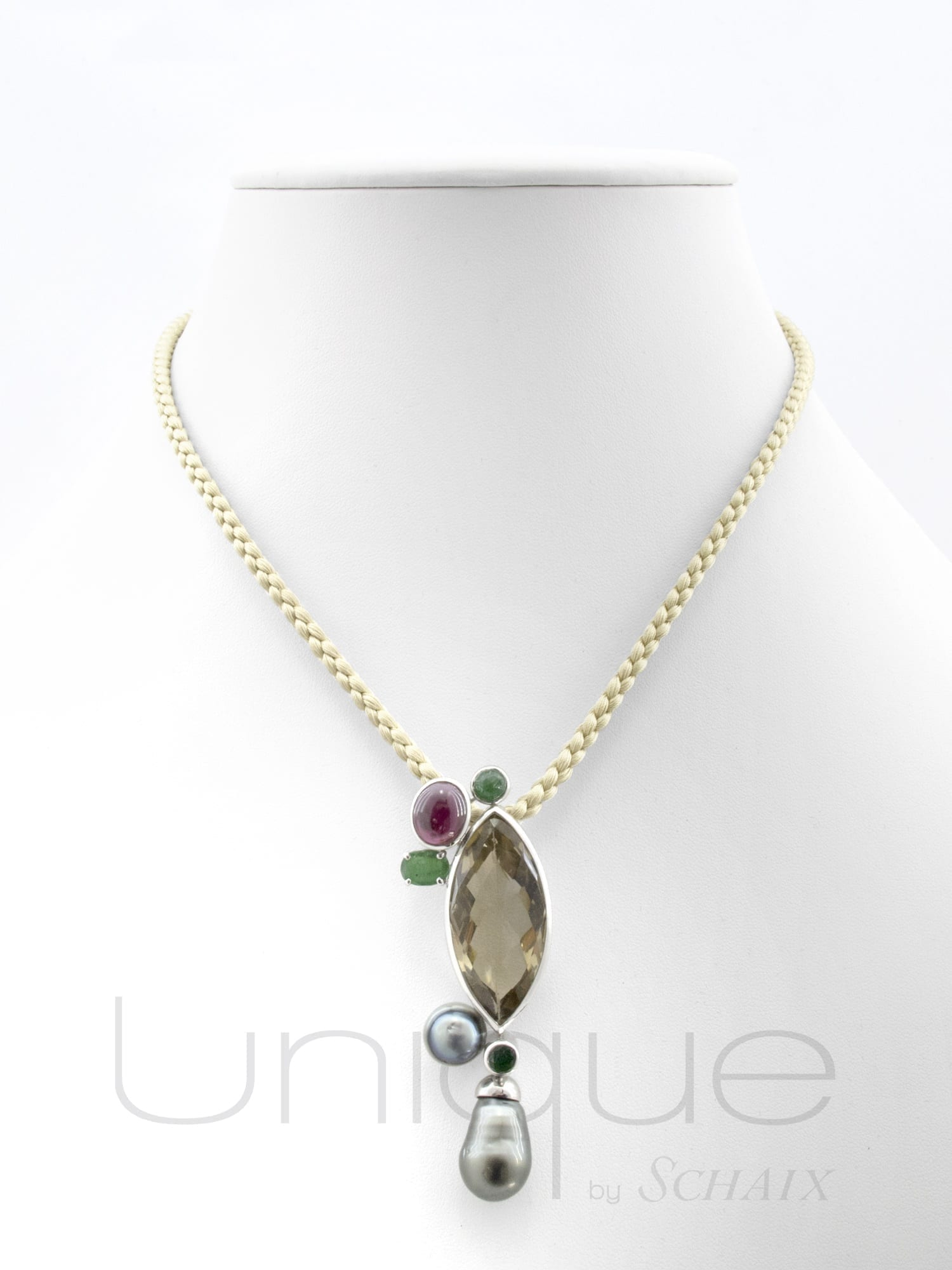 Silk thread in beige with a silver pattern, a smoky quartz marquise, emerald and a garnet cabochons and circled Tahiti pearls. Silver clasp.