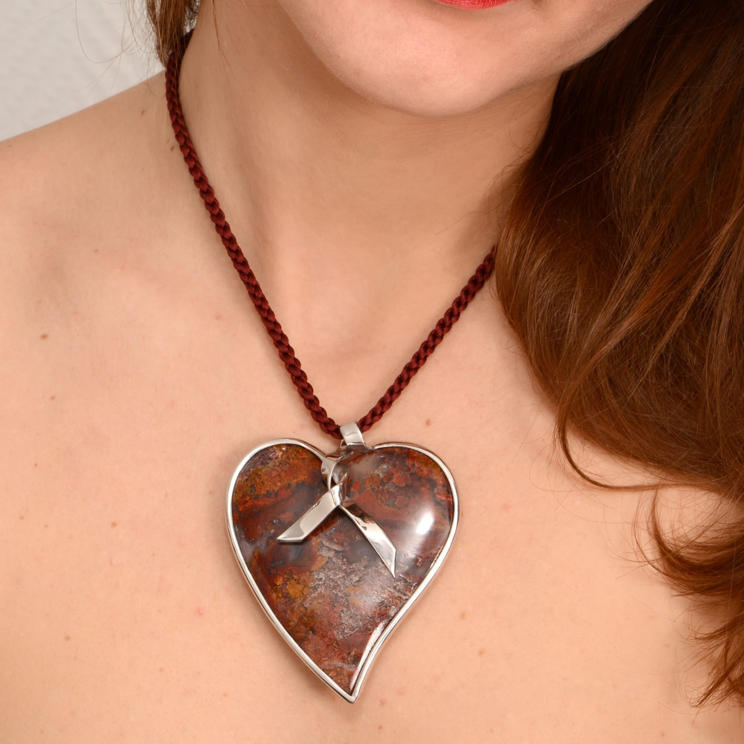 Silk thread with a heart-shaped pendant set with silver ribbon.