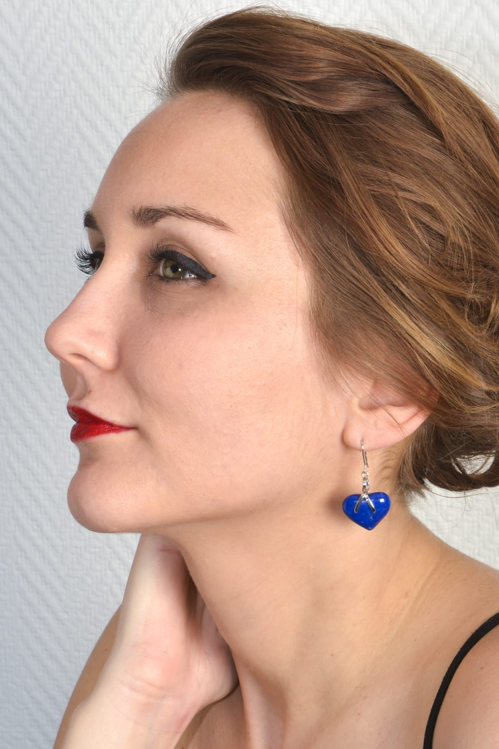 Silver earrings with two heart-shaped lapis-lazuli gemstones.